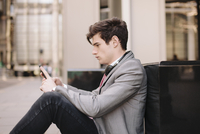 Young city businessman sitting on sidewalk reading smartphone messages