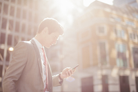 Young city businessman reading smartphone texts whilst walking