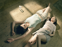 Two young women lying on wooden floor in sunlight