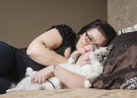 Portrait of Ragdoll cat with owner, relaxing on bed