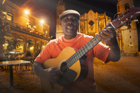 Senior man playing acoustic guitar in Plaza de la Catedral at night, Havana, Cuba