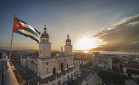 Cuban flag over Plaza de la Catedral at sunset, Santiago de Cuba, Cuba