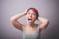 Studio portrait of young woman with hands in hair shouting