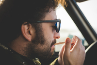 Close up of mid adult man in car lighting a cigarette