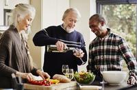 Senior man pouring wine in kitchen, woman preparing food