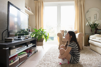 Girl sitting on rug watching the television