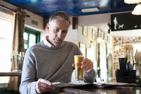 Mature man drinking beer and reading newspaper in pub