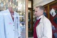 Mature man looking at suit jacket in tailors shop window