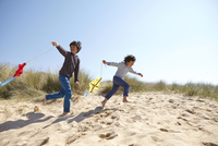 Two young boys, flying kites on beach