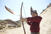 Young boy wearing fancy dress, holding home-made bow and arrow