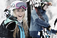 Mid adult woman holding skis, laughing