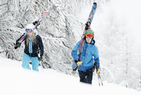 Man and woman walking in snow with skis