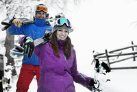 Man and woman carrying skis