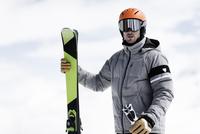 Man wearing helmet and ski goggles holding skis, portrait