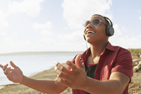 Young man on beach wearing headphones and sunglasses, arms raised 11015255135| 写真素材・ストックフォト・画像・イラスト素材|アマナイメージズ