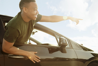 Young man leaning out of car window pointing and smiling