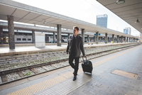 Young businessman commuter walking along train station platform pulling suitcase.