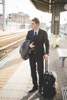 Young businessman commuter standing on railway platform with suitcase.