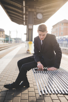 Portrait of young businessman commuter using digital tablet at train station.