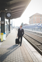 Portrait of young businessman commuter walking along railway platform.