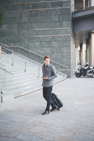 Young businessman commuter walking with suitcase.