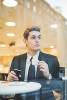 Portrait of young businessman sitting in cafe using digital tablet and mobile phone.