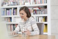 Mid adult woman at home, using laptop 11015255386| 写真素材・ストックフォト・画像・イラスト素材|アマナイメージズ
