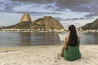 Mid adult woman sitting in beach, reading book, Sugarloaf mountain in background, Botafogo bay, Rio de Janeiro, Brazil