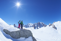 Male and female skiers looking out from ridge on Mont Blanc massif, Graian Alps, France