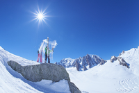 Male and female skiers shaking snow from skis on Mont Blanc massif, Graian Alps, France