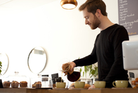 Cafe waiter pouring fresh filter coffee into cups