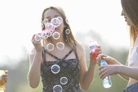Two teenage girls blowing bubbles in park 11015255637| 写真素材・ストックフォト・画像・イラスト素材|アマナイメージズ