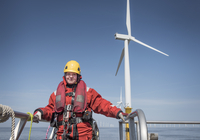 Portrait of female engineer on boat at offshore windfarm