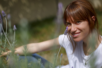 Mid adult woman sitting among lavender, looking at camera, smiling