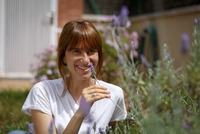 Mid adult woman sitting smelling lavender, smiling at camera