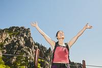 Female hiker with arms raised on way to Daecheongbong peak,  Seoraksan National Park in South Korea