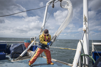 Scientist bringing plankton net on board of research ship