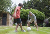 Grandfather and grandson playing with football in garden