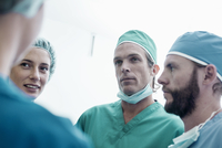 Four male and female surgeons having discussion in hospital