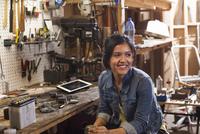 Portrait of female mechanic in workshop, looking away, smiling