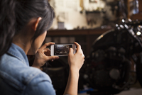 Female mechanic in workshop, taking photograph of motorcycle using smartphone