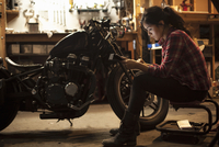 Female mechanic working on motorcycle in workshop