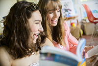 Two young female friends browsing and laughing at books
