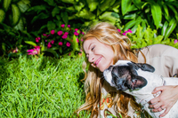 Dog licking woman's face in garden