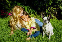 Mature woman, daughter and dog sitting in garden grass