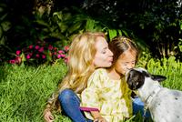 Dog licking girl's face in garden