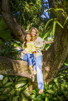 Mother and daughter sitting on garden tree branch