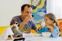 Mature man, and daughter sharing tea