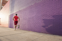 Rear view of male runner running along sidewalk