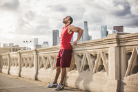 Male runner leaning back taking a break on bridge, Los Angeles, California, USA